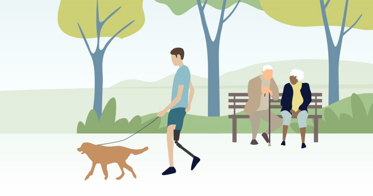 A guy is walking his dog in a park. A couple is sitting down on a bench.